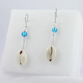 Boucles d'oreilles longue perle et coquillage cauris sur chaîne.